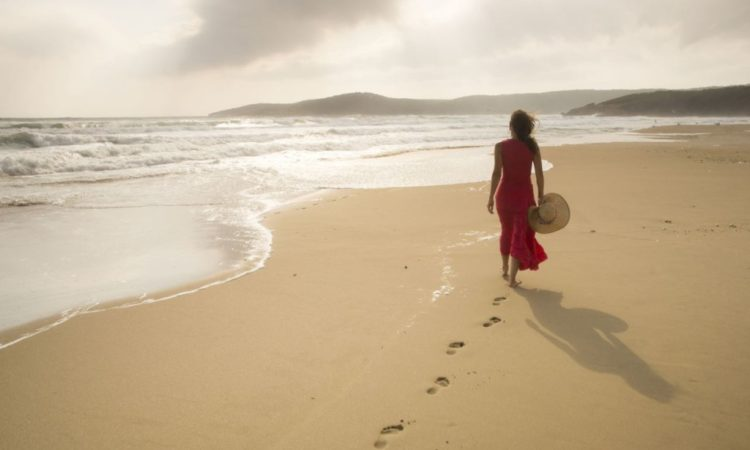 -woman-in-red-walking-on-beach-