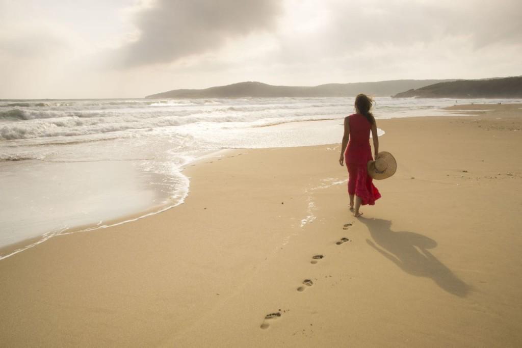 -woman-in-red-walking-on-beach-