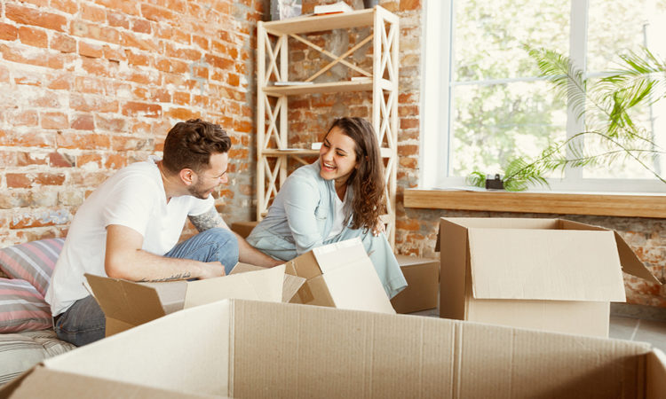 Young Couple Moved To A New House Or Apartment. Unpacking Cardbo